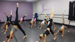 On of our assistants working with our jazz 2 girls on their leg extensions.  Lengthen through the backs of those legs girls!